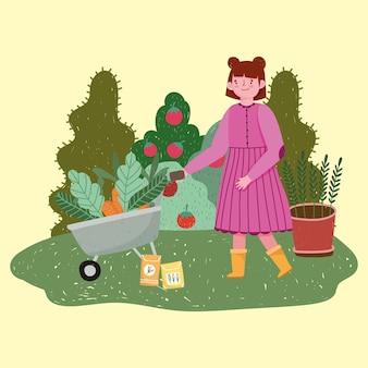 Девушка-садовник с тачкой с морковью и семенами на траве