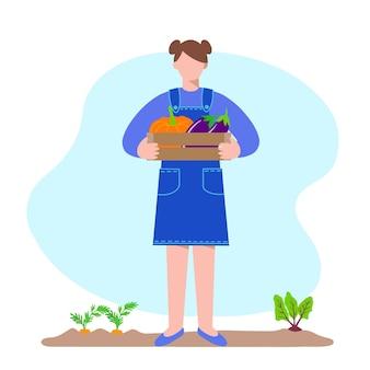 Садоводство. молодая женщина держит деревянную коробку с овощами, тыквой и баклажанами.