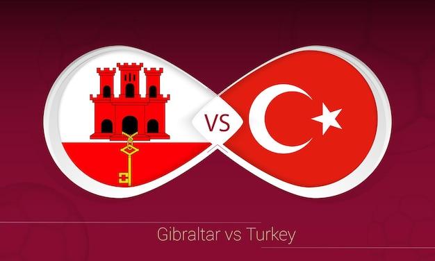 Гибралтар против турции в футбольном соревновании, группа g. versus значок на футбольном фоне.