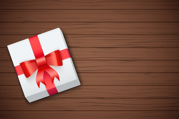 Gift box on brown wooden table.