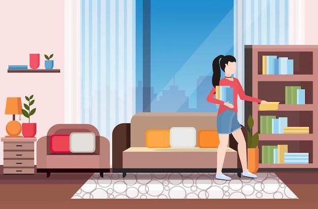 Домохозяйка чистка деревянная книжная полка с помощью пыли ткань girk делать домашнее хозяйство уборка концепция современная гостиная интерьер полная длина квартира горизонтальный