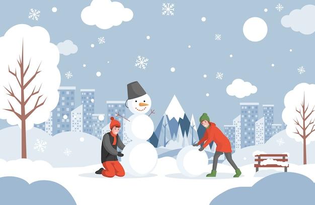 Девочка и мальчик в теплой зимней одежде лепят снеговика в парке