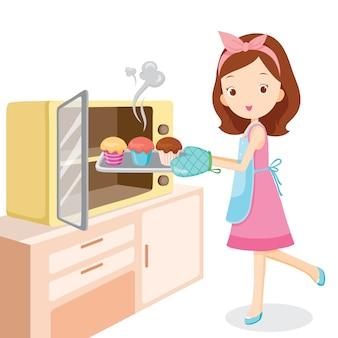 부엌에서 오븐으로 컵 케이크를 굽는 소녀
