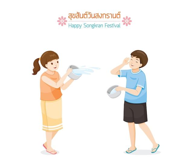 Girl and boy splashing water together tradition thai new year suk san wan songkran translate happy songkran festival