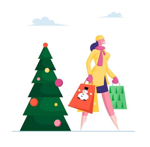 Девушка с бумажными пакетами проходит мимо украшенной ели