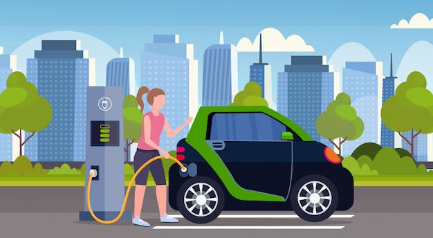 Girl charging electric car at city electrical charge station renewable eco technologies clean transport environment care concept  modern cityscape background full length