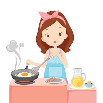 キッチンで朝食に目玉焼きを調理している女の子