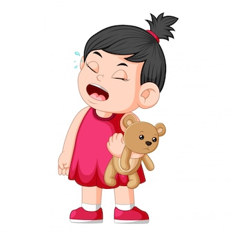 A girl crying while holding a brown teddy bear
