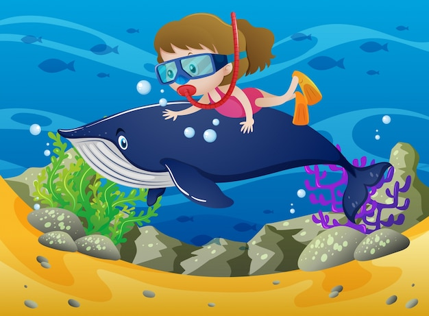 Girl diving with whale under the sea
