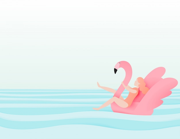 Girl floating on the beach with flamingo