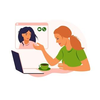 ガールフレンドはオンラインでチャットします。ノートパソコンの前の椅子に座って、友達と話す女の子。ビデオ会議、オンラインチャットの概念。自宅からの仕事またはオンライン会議。
