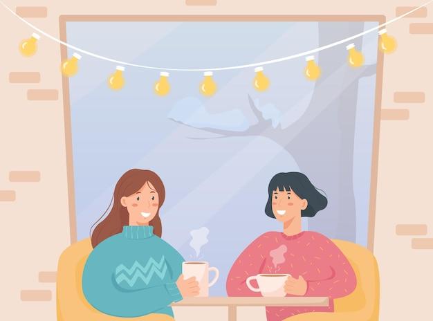 冬の日にカフェに座って、大きな窓の近くでお茶やコーヒーを飲むガールフレンド。レンガの壁とランプのある居心地の良いカフェ。冬時間と冬の活動