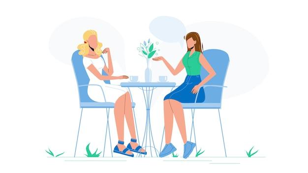 Подруги говорят и пьют кофе в кафе