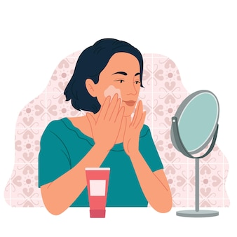 A girl in front of a table mirror applies cream on her face