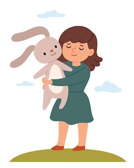 The girl in a green dress hugs a teddy rabbit