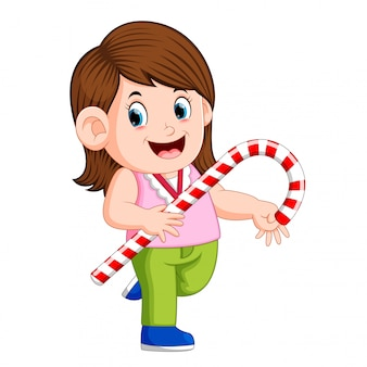 A girl holding big christmas candy cane