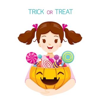Girl holding halloween pumpkin bucket full of sweets