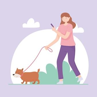Girl holding phone walking dog