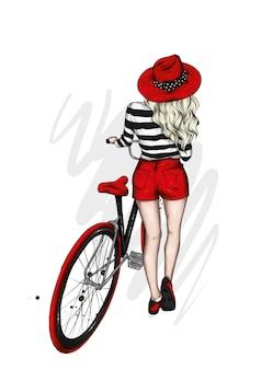 Девушка в стильной шляпе и шортах и велосипеде