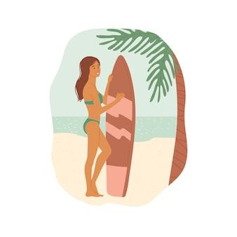 Девушка в купальнике с доской для серфинга стоит на пляже под пальмой на фоне океана.