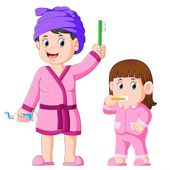 The girl is brushing her teeth with her mother beside her