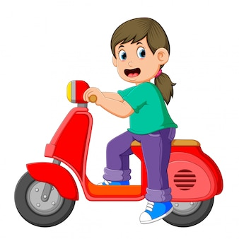 The girl is posing on the red scooter