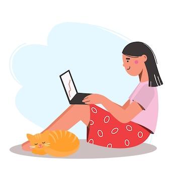 Девушка сидит на полу с ноутбуком на коленях. рядом лежит рыжий кот. работа на дому.