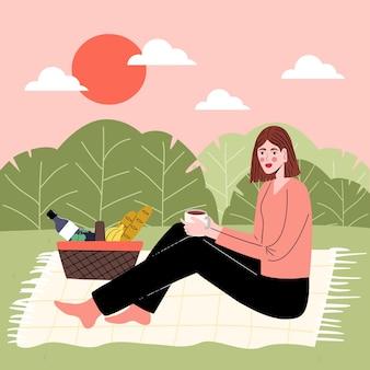 소녀는 잔디에 앉아 피크닉 캠핑