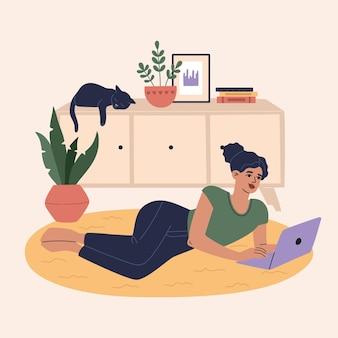女の子はカーペットの上に横たわり、快適な部屋でラップトップを操作します。箪笥で眠っているかわいい猫。リモートジョブと学習ワークスペースの概念、自宅の労働者。フラット漫画イラスト