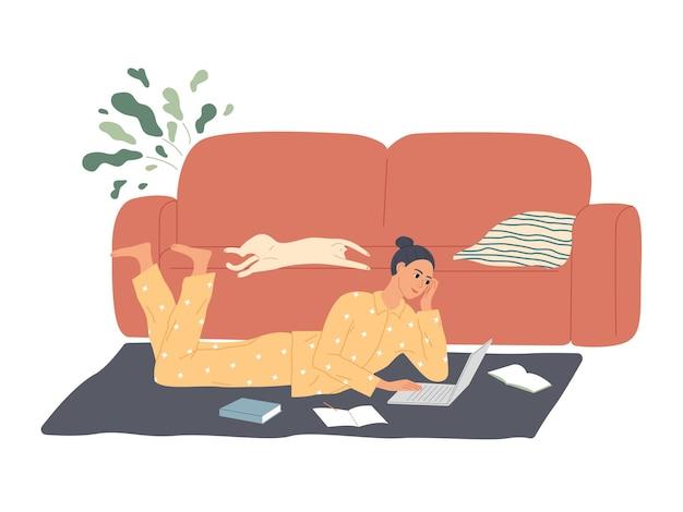 Девушка лежит на полу с ноутбуком, учит уроки, делает домашнее задание.