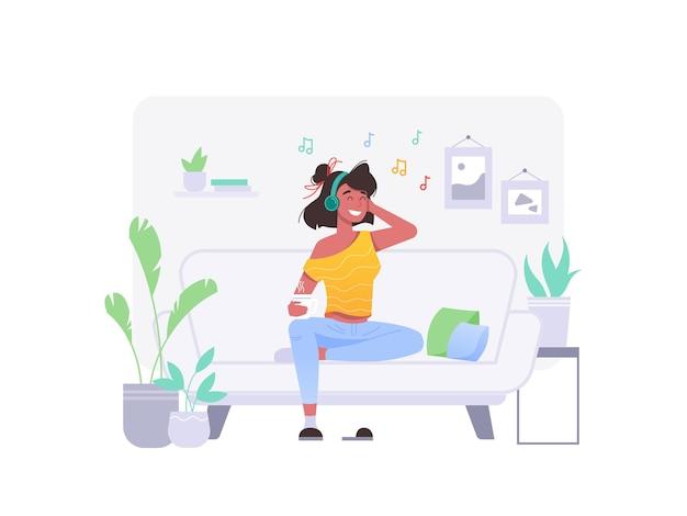 Девушка слушает музыку на диване у себя дома в наушниках