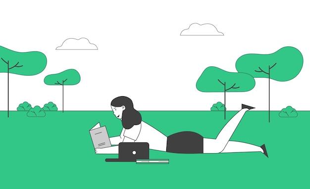 Девушка лежит на траве и читает книгу в школе