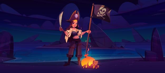 Ragazza pirata sulla spiaggia notturna con bandiera jolly roger e spada vicino al fuoco ardente