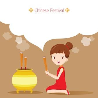 Девушка молится и выражает почтение китайскому богу удачи, традиционный китайский фестиваль