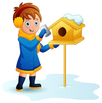 Girl puts a letter into the mailbox in winter