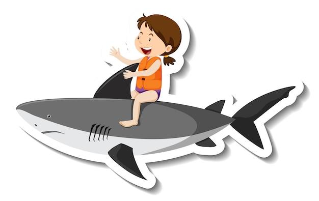 Una ragazza cavalca un adesivo gonfiabile del fumetto dello squalo