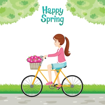Girl riding bicycle with flower in basket front of bicycle