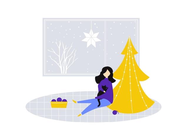 소녀는 방의 아늑한 겨울 장면을 부분적으로 장식한 고양이를 안고 앉아 있다