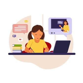 그의 컴퓨터를 사용하여 온라인 공부하는 그의 책상 뒤에 앉아 소녀