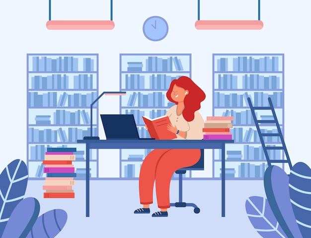 Girl sitting at desk in library and reading book. cheerful lady studying, looking at laptop screen. shelves with books in background. education, knowledge concept