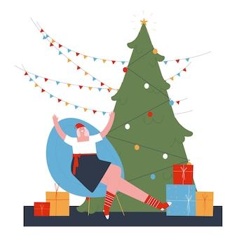 クリスマスツリーの横にある肘掛け椅子に座っている女の子