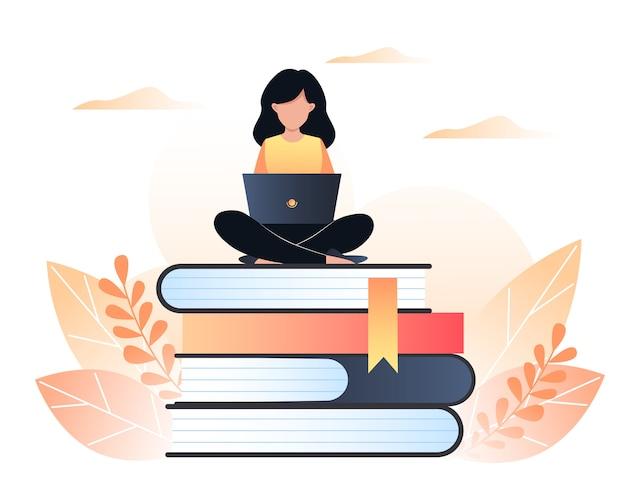 本、オンライン教育の概念のラップトップで座っている女の子