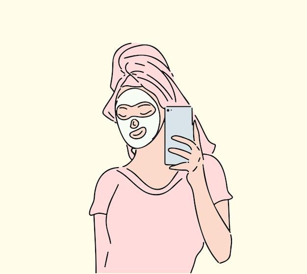 소녀는 그녀의 얼굴 피부를 돌보는 편안한 시간을 보냅니다.