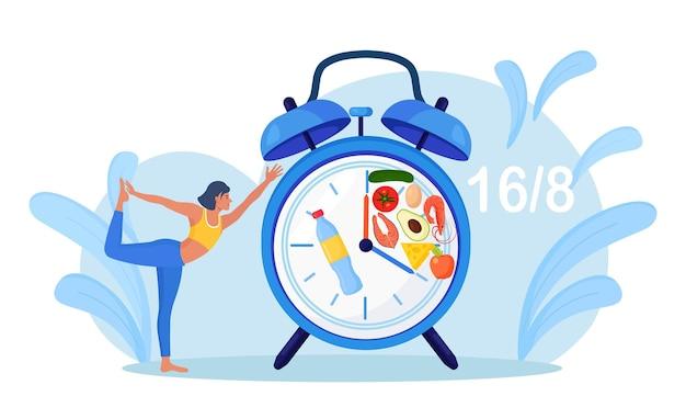 食べる時間を待っている木のポーズでバランスの取れた女の子のスタンド。ヨガ。忍耐。断続的な断食。スポーツ、フィットネスをしている女性。ダイエット、適切な栄養。時間制限のある食事。食物摂取時計