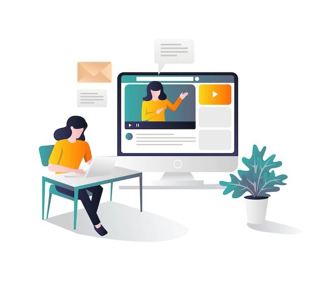 Девушка учится за столом с учебником на компьютере