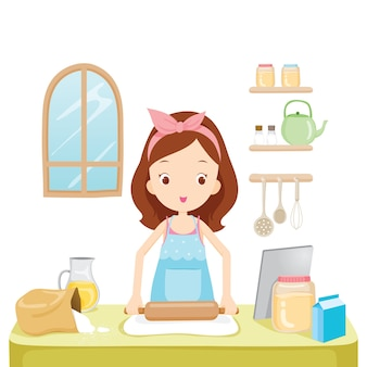 Girl thresh flour with tablet in kitchen