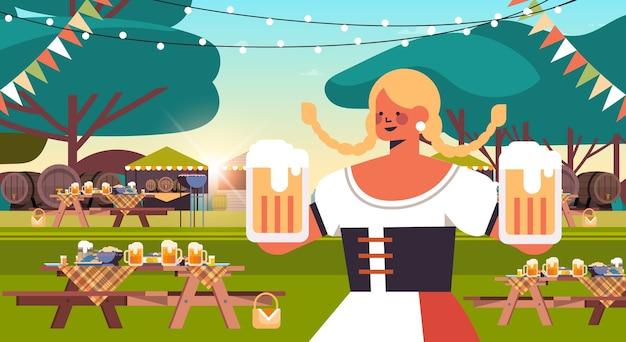 Девушка официантка держит пивные кружки октоберфест вечеринка концепция празднования женщина в традиционной немецкой одежде веселится