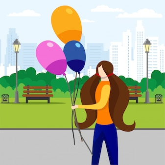 Girl walking in city park with bunch of balloons.