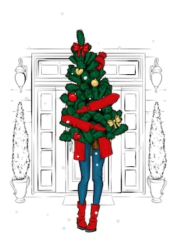 Girl in winter clothes with a christmas tree.