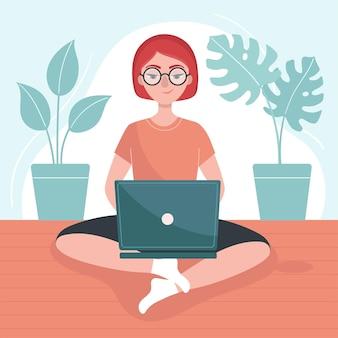 ノートパソコンを持った女の子が床に座っています。フリーランスの概念、自宅での仕事。家にいる。